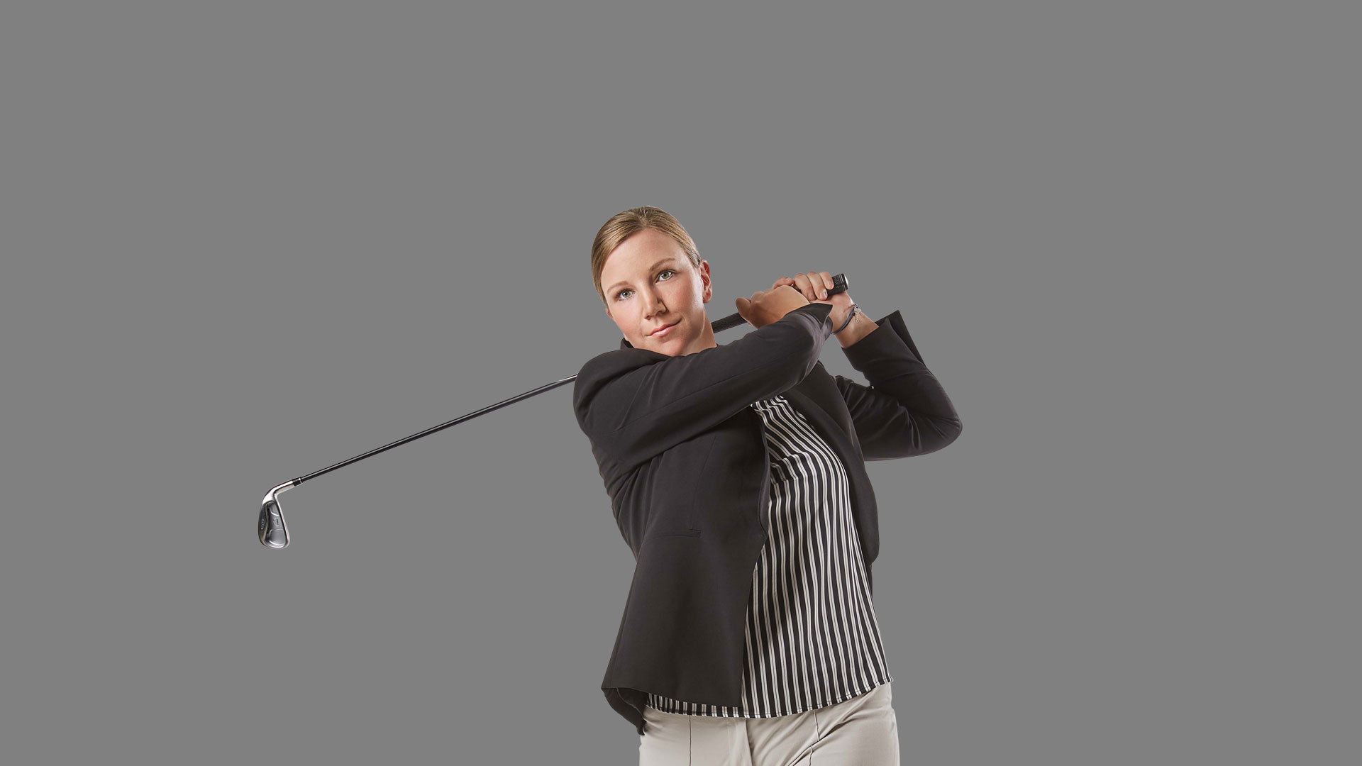Employee Christiane swinging a golf club
